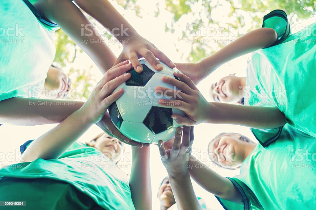 Diverse teammates huddle together to cheer before soccer game stock photo