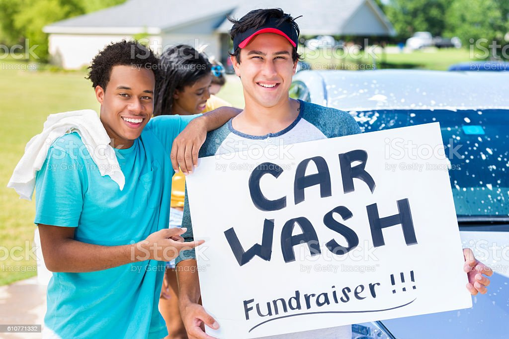 Diverse teenage boys hold 'Car Wash' fundraiser sign stock photo