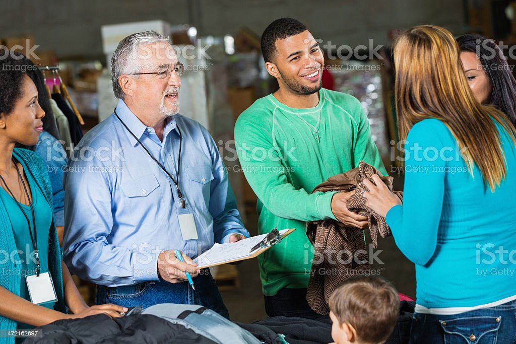 Diverse volunteers accpeting donations at charity coat drive royalty-free stock photo