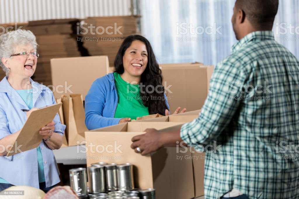Cheerful diverse group of volunteers work together packing canned...