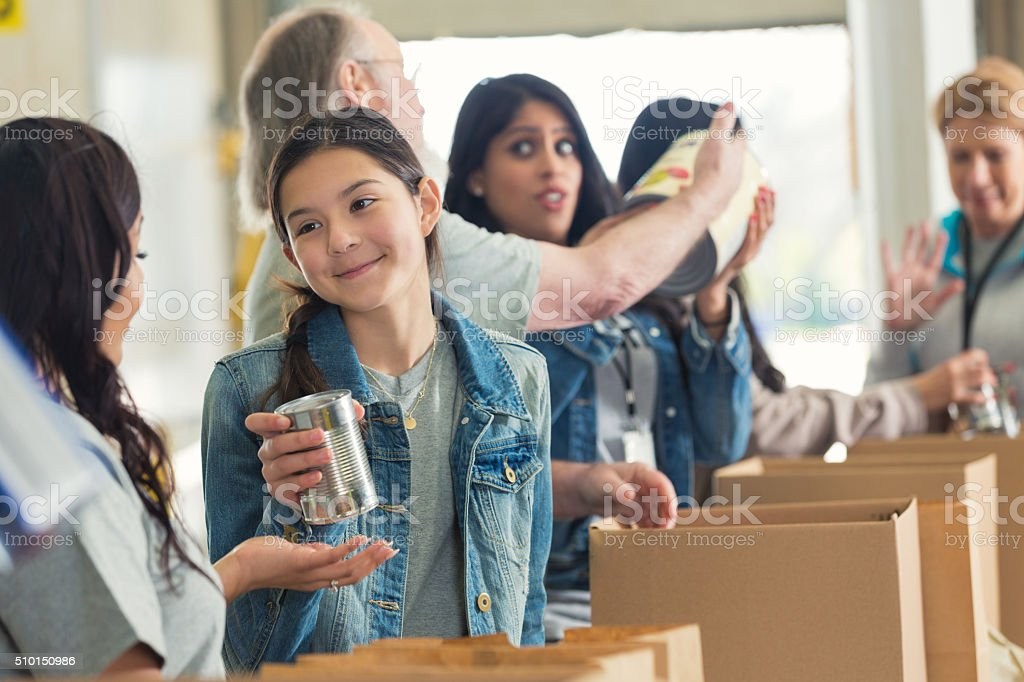 Diverse volunteers packing boxes at food drive stock photo