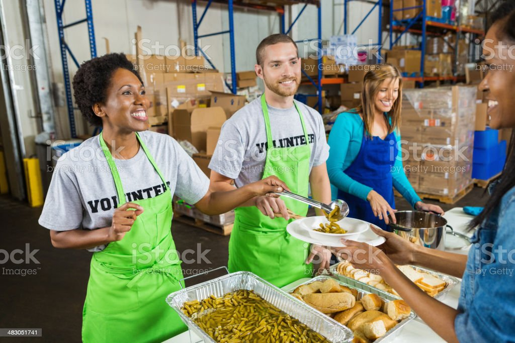 Diverse volunteers serving hot meal at soup kitchen stock photo