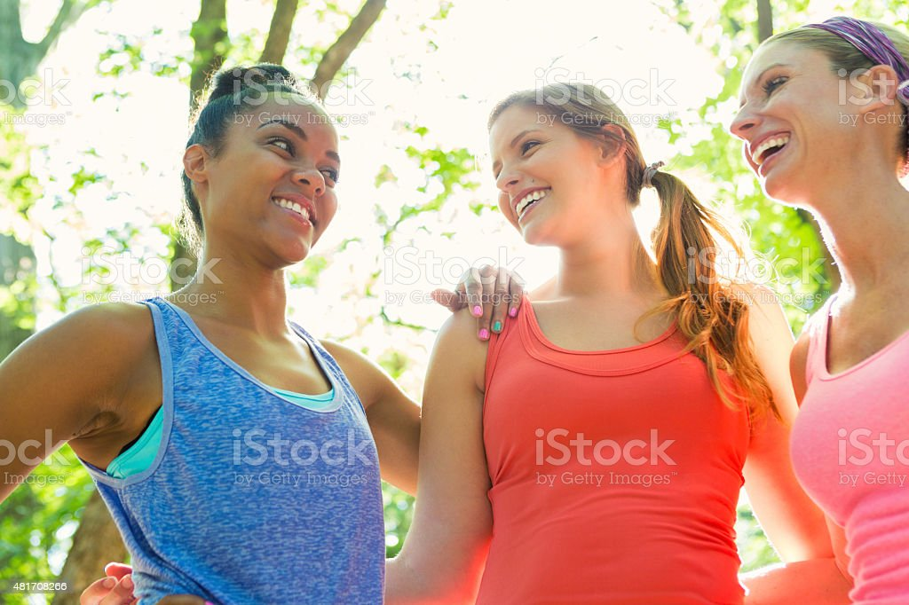 Diverse women exercising together in park on sunny day stock photo