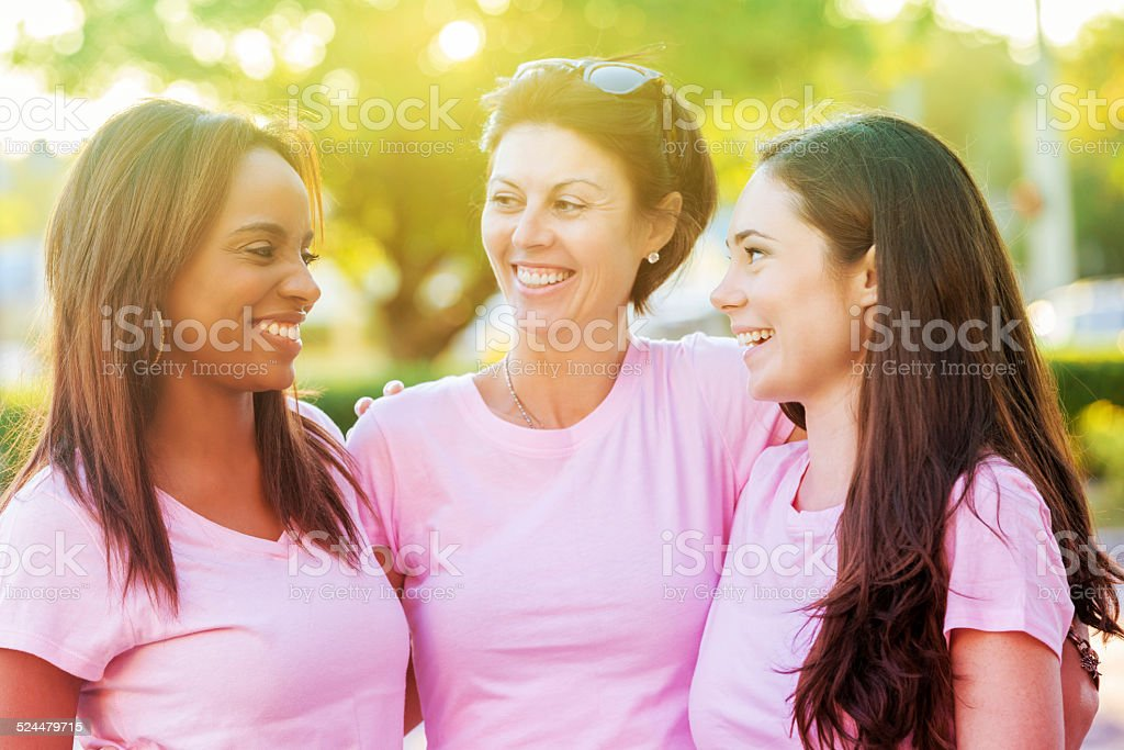 Diverse women smiling after running in breast cancer awareness race stock photo
