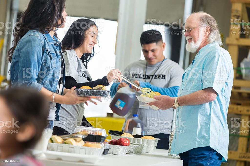 Diverse young adults volunteering to serve meal to seniors stock photo