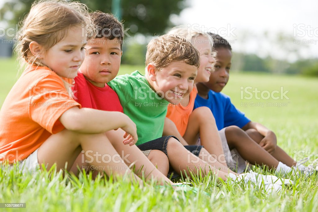 Diverse young children sitting together in a row royalty-free stock photo