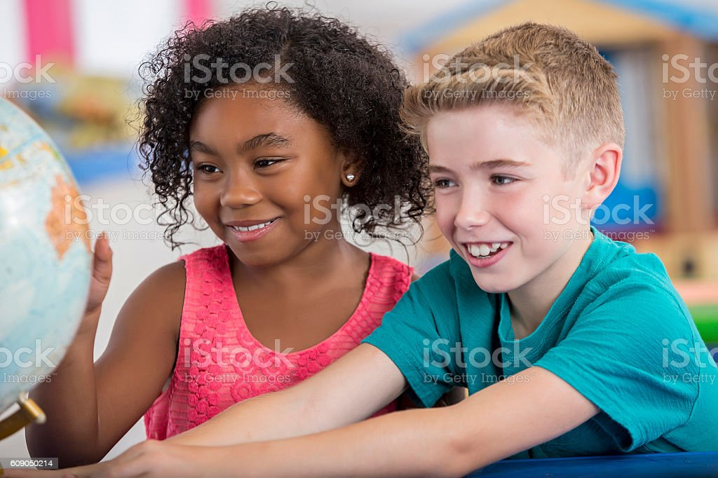 Diverse young friends study a globe together stock photo