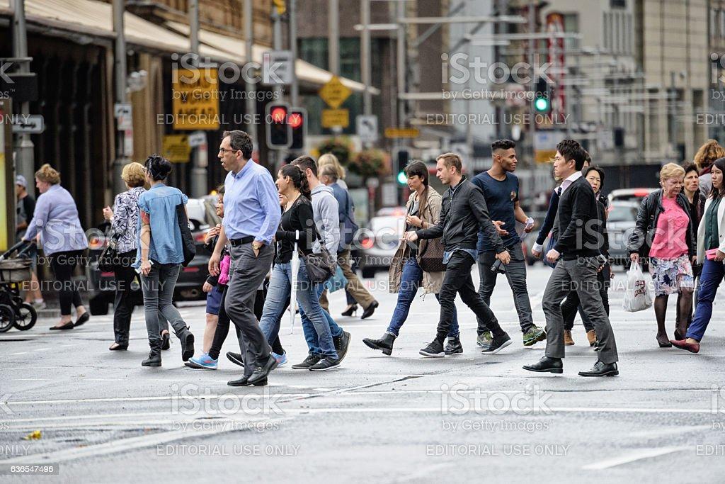 Diversified people crowd crossing rain wet street. Scene from central...