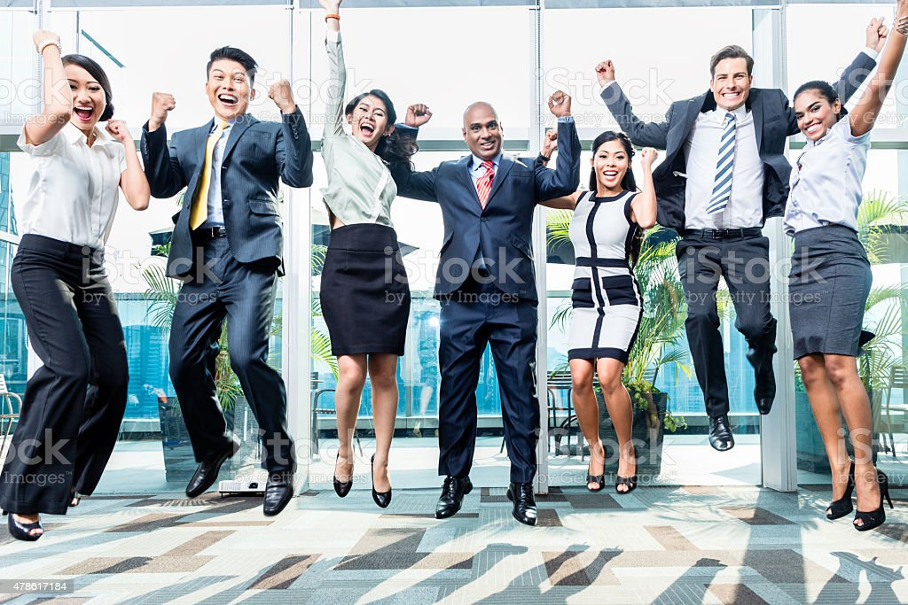 Diversity business team jumping celebrating success stock photo