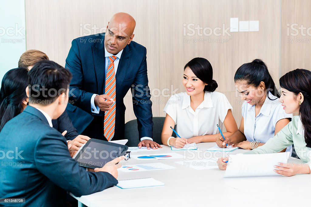 Diversity team in business development meeting with charts stock photo