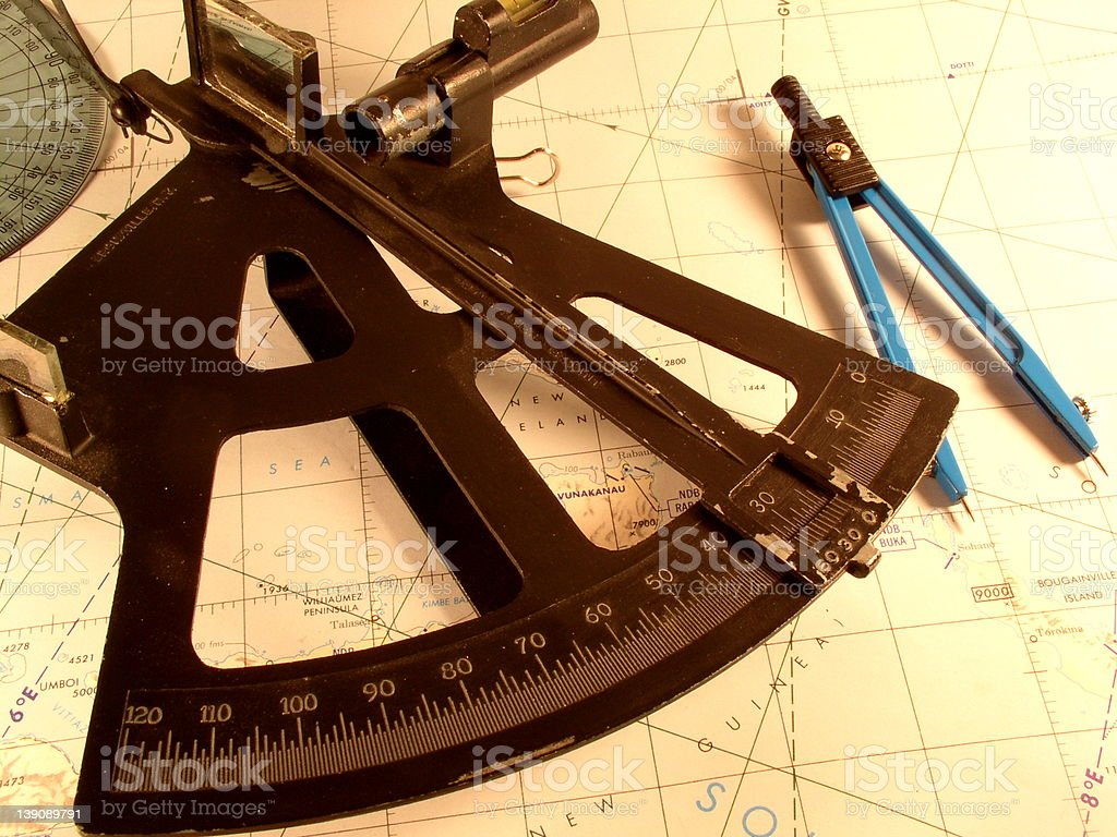 Dividers, protractor, and sextant on top of chart South Seas stock photo