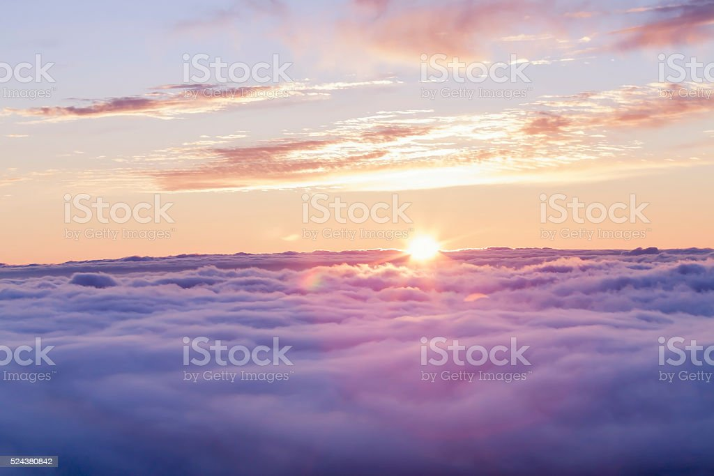 Divine sunset above the clouds stock photo