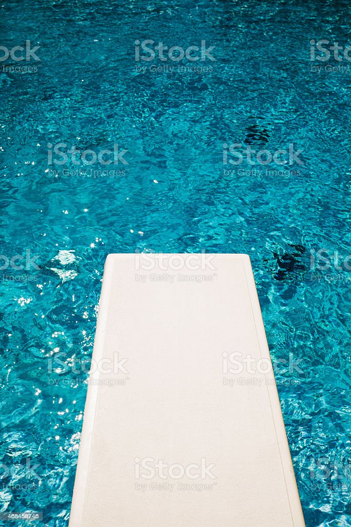 Diving board into outdoor swimming pool stock photo