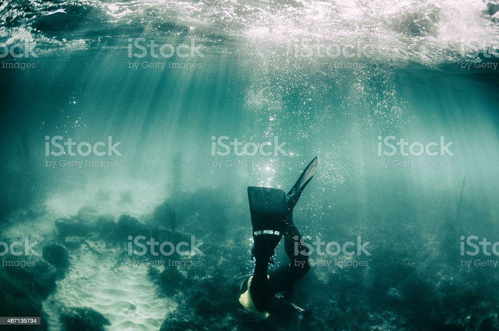 Diving down, a diver goes to the sea floor stock photo