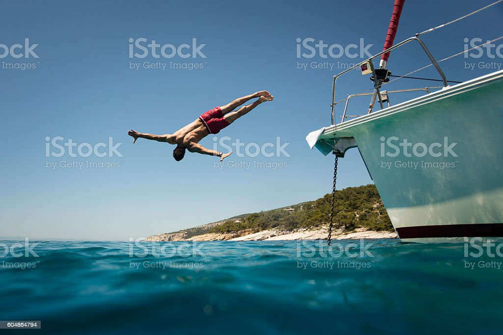 Diving into the sea from yacht stock photo