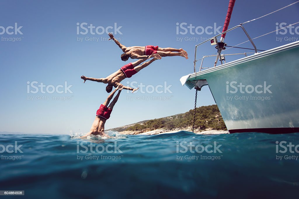 Diving into the sea from yacht sequence shoot stock photo