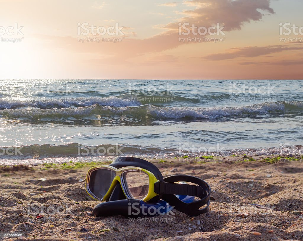 Diving mask on a sandy beach against the sea stock photo