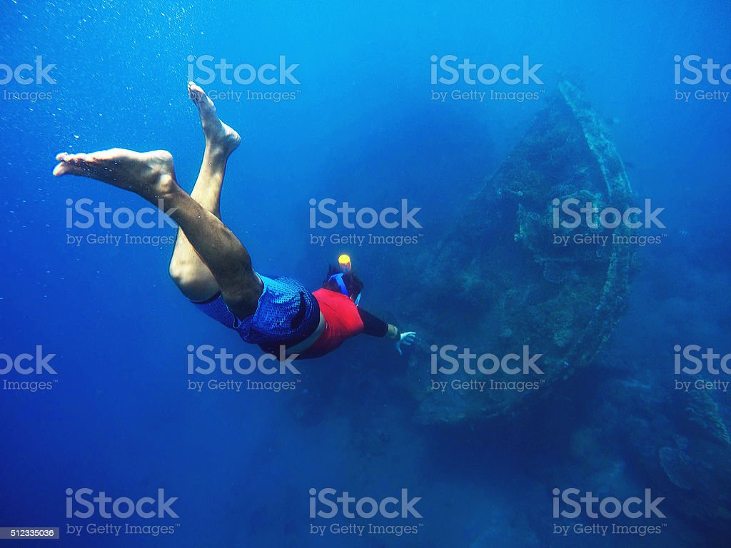 Diving to the shipwrecks, snorkeler in the deep blue sea stock photo