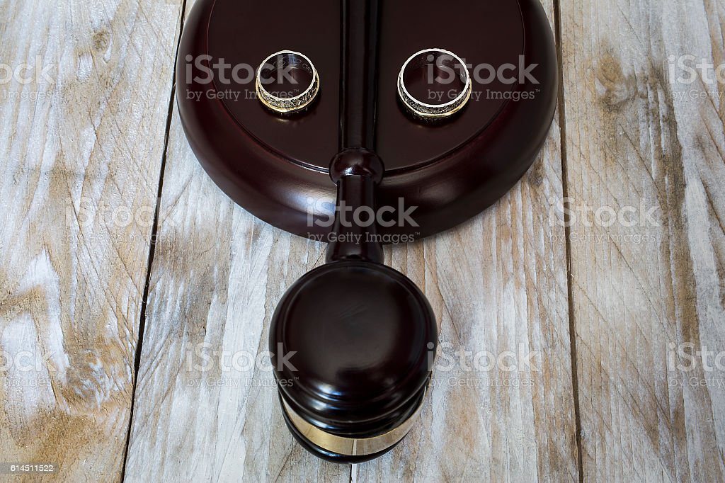 Divorce concept. Close up of wedding rings and judge gavel stock photo