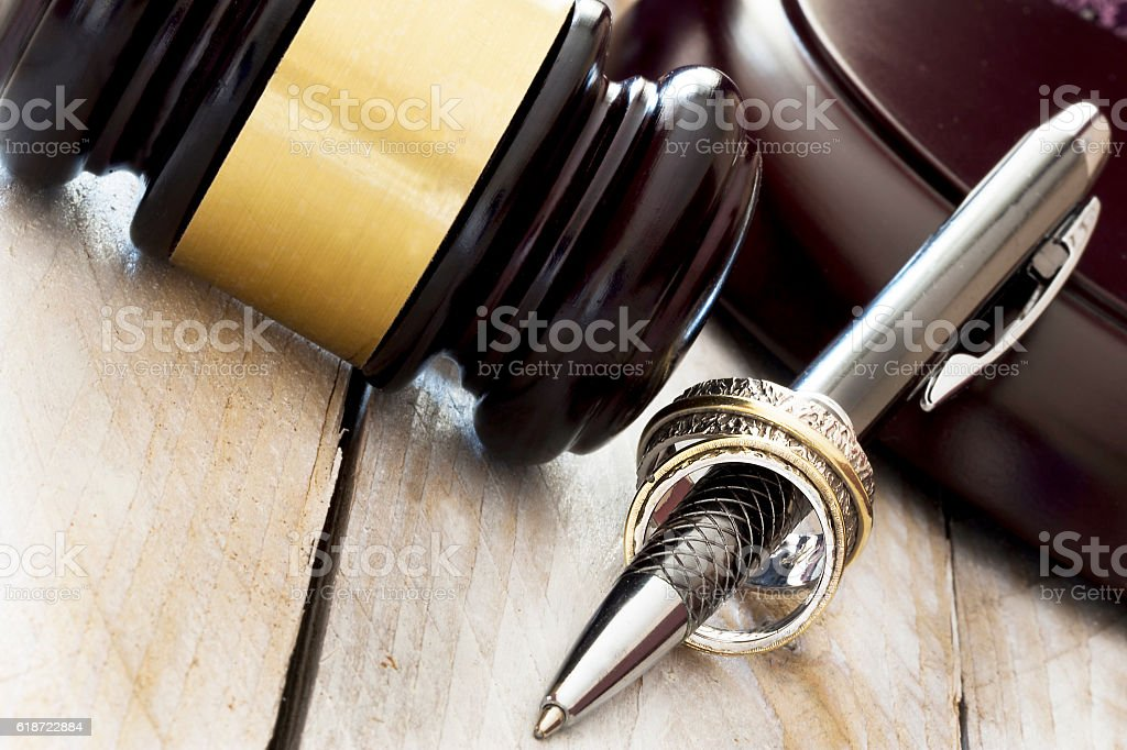 Divorce concept. Judge gavel, wedding rings and tie stock photo