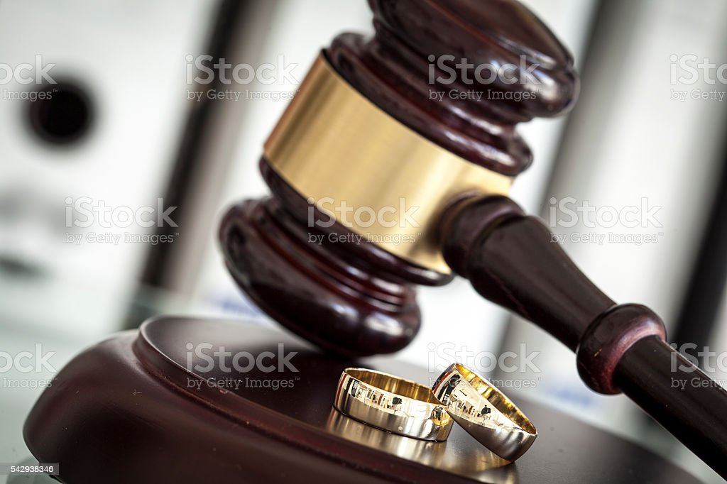 Divorce concept with gavel and wedding rings stock photo