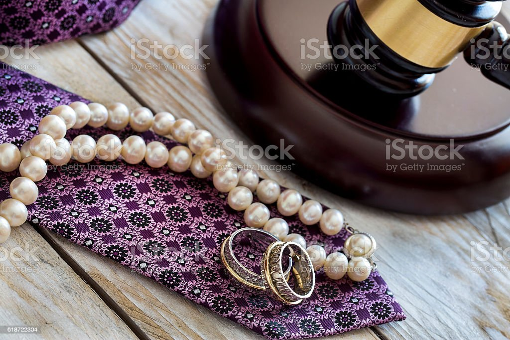 Divorce law concept. Judge gavel, rings, tie and pearl necklace stock photo