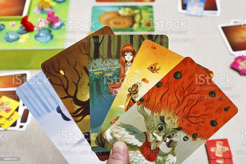 Dixit game cards in hand stock photo