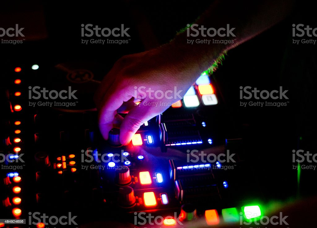 dj hand controlling mixing desk stock photo