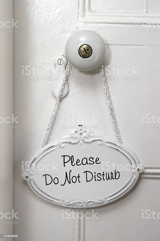 Do Not Disturb sign handing over a white doorknob stock photo