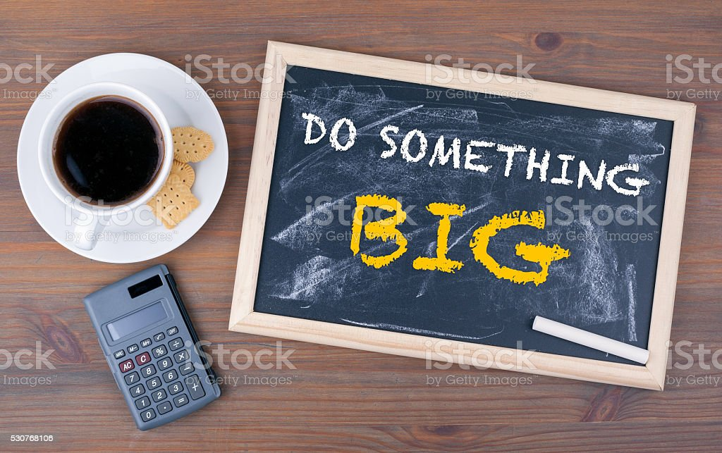 Do Something Big. Chalk board on a wooden table stock photo