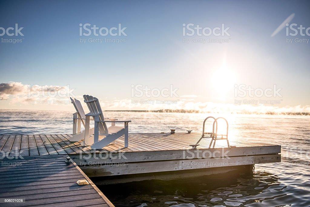 Dock and muskoka chairs at sunrise stock photo