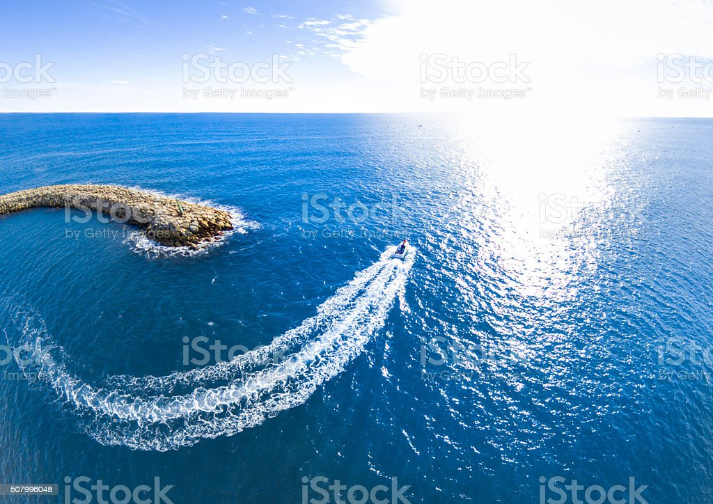 dock boat speed wave sun flare horizon curve port stock photo