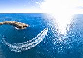 dock boat speed wave sun flare horizon curve port