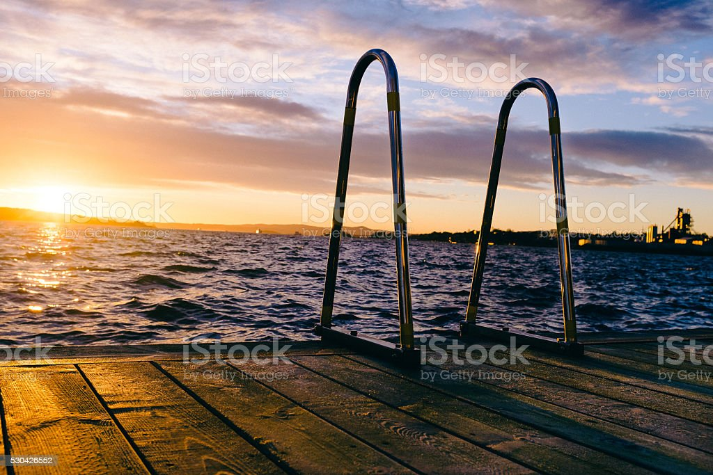 Dock ladder at sunset stock photo