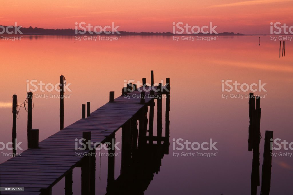 Dock on Calm Water at Sunset royalty-free stock photo