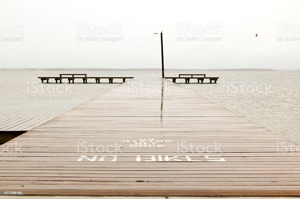 Dock overlooking the bay on a rainy day stock photo