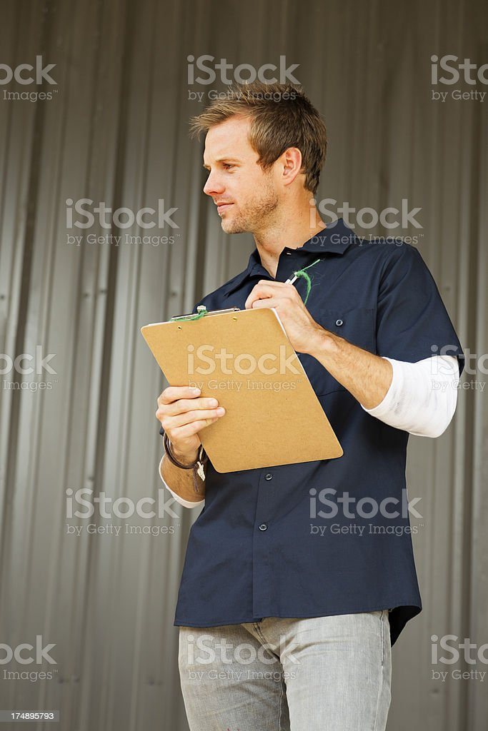 Dock supervisor tracking activities on his clipboard royalty-free stock photo
