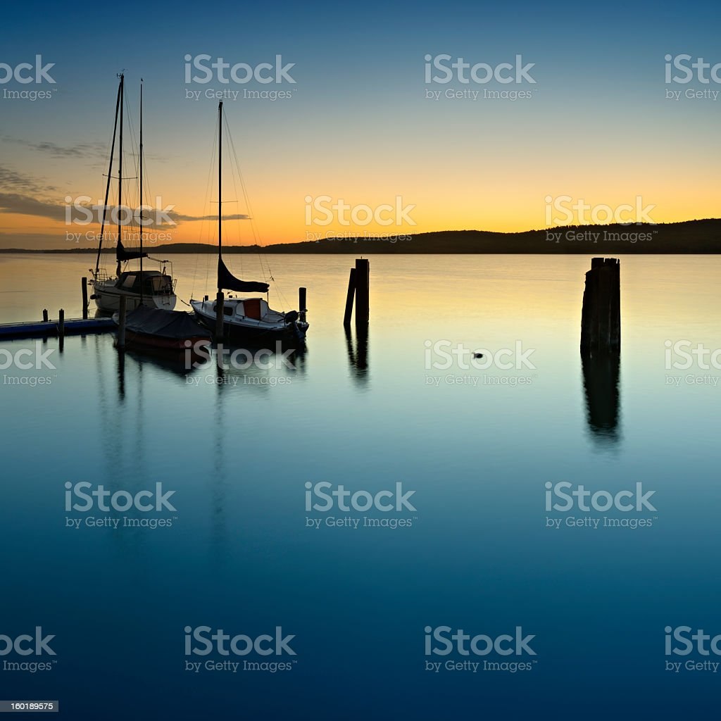 Dock with Sailboats on a Calm Lake at Sunrise stock photo