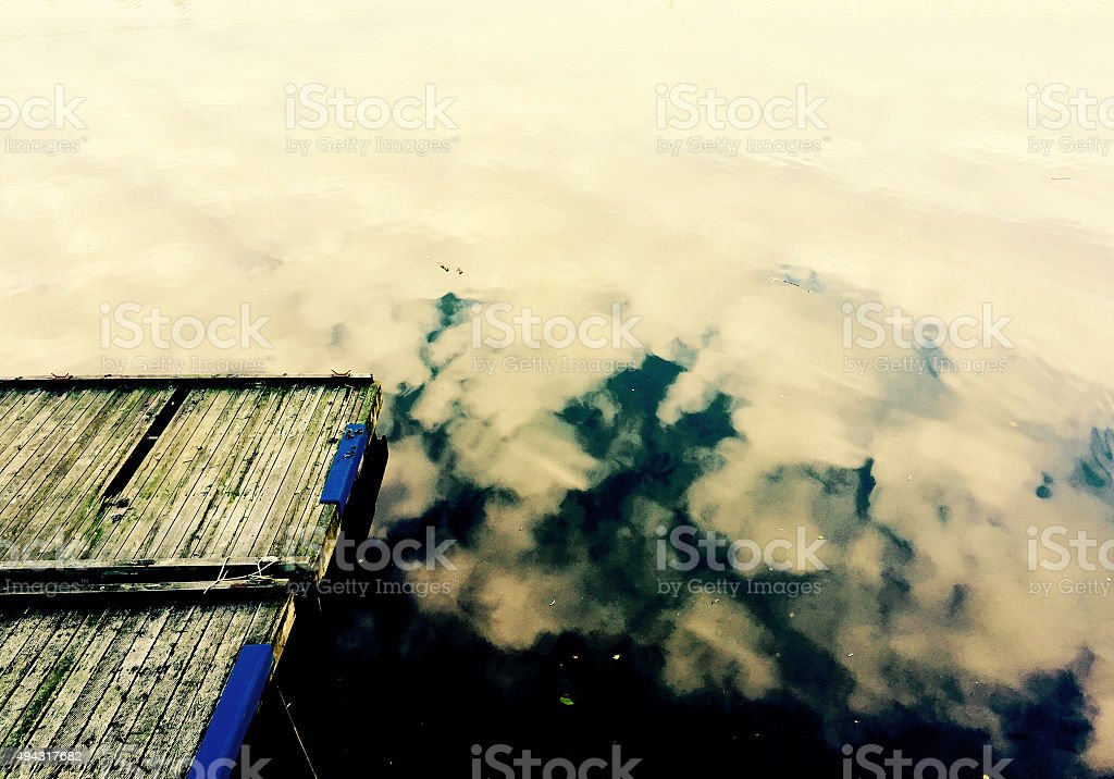 Dock with the cloud reflection on lake royalty-free stock photo