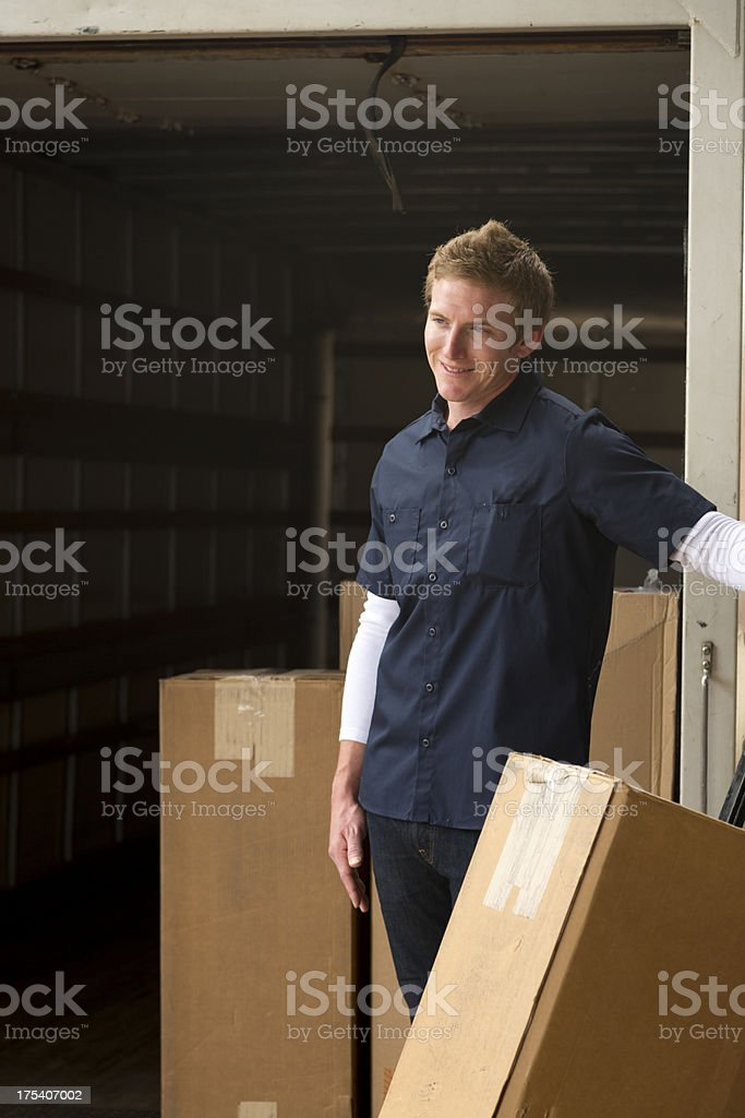 Dock worker loading boxes into a truck stock photo