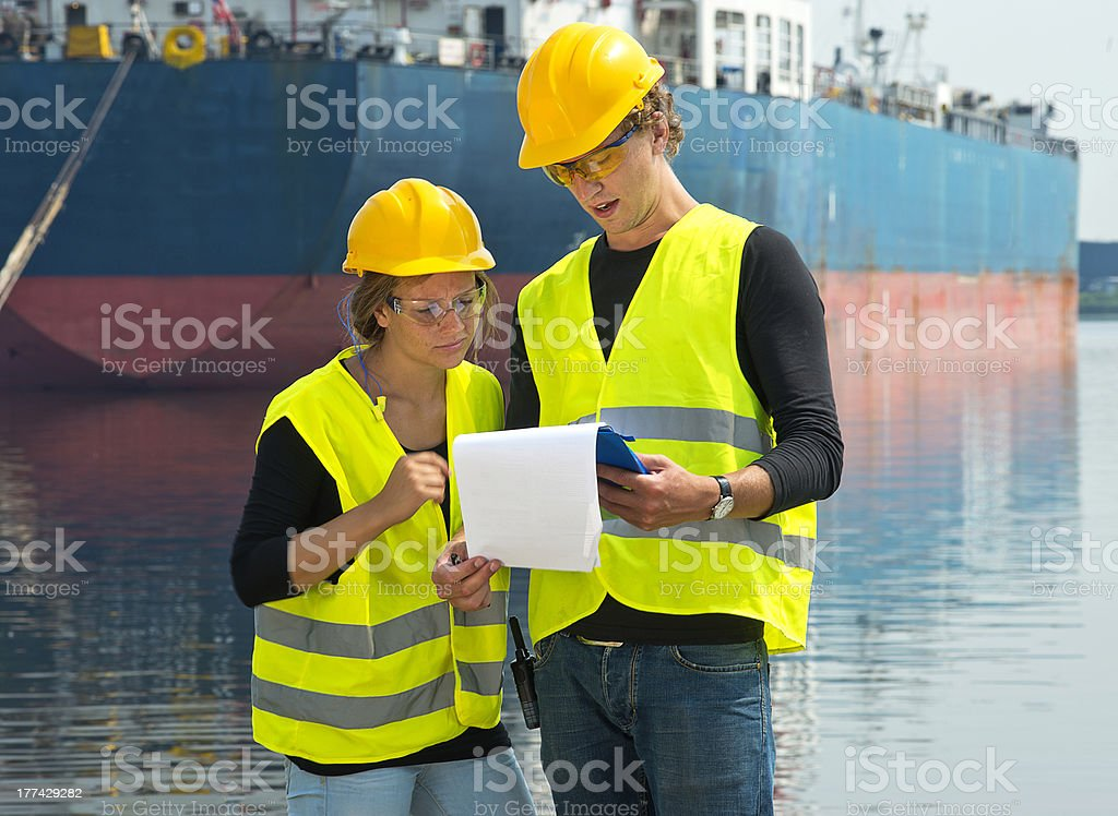 Dockers checking freight papers stock photo