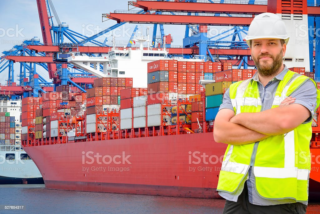 Dockworker in port in front of container ships. stock photo