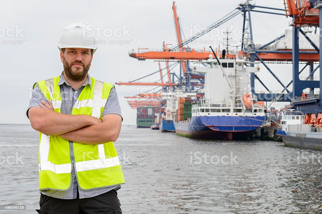 Dockworker standing in front of container ships in port stock photo