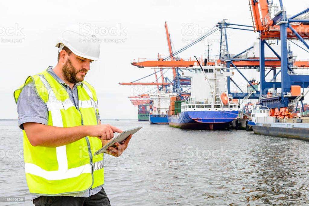 Dockworker with tablet computer stock photo