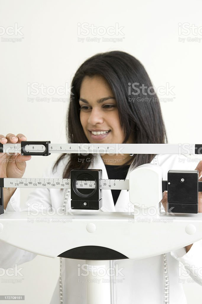 doctor adjusting weight scale royalty-free stock photo