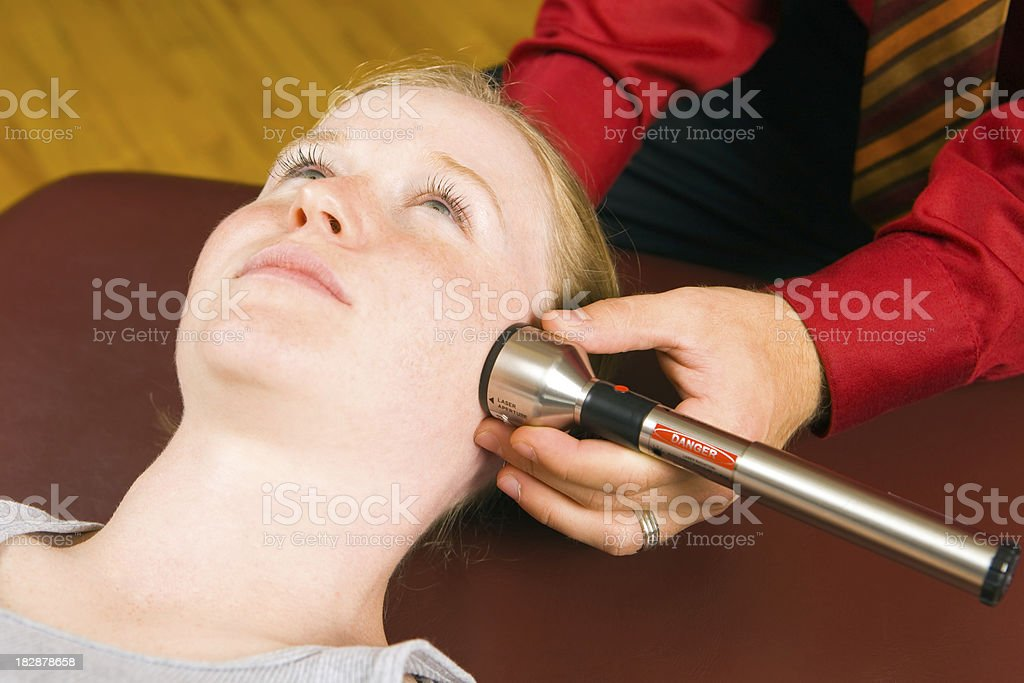 Doctor Administering Cold Laser Therapy Treatment to Female Patient's Face royalty-free stock photo