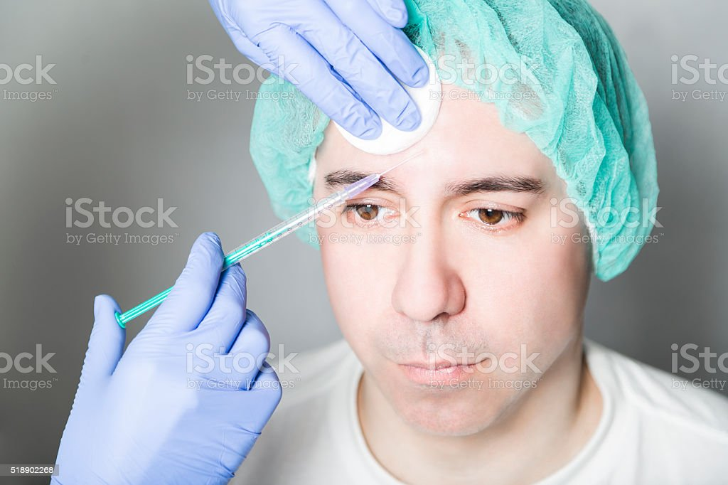 Doctor aesthetician makes face beauty injections to male patient stock photo