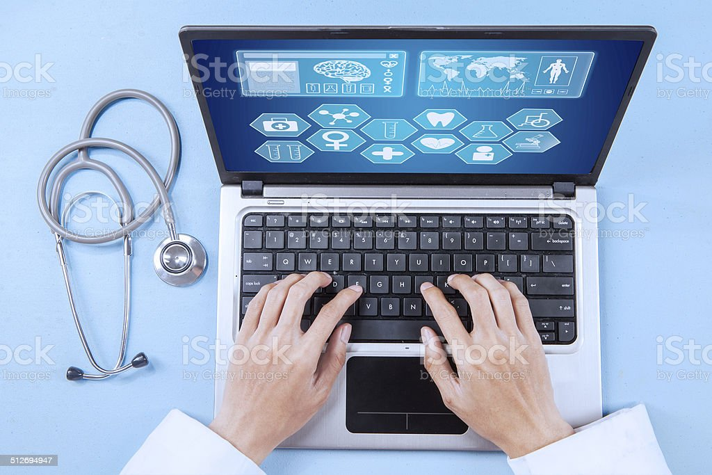 Doctor analyzing human illness on laptop stock photo