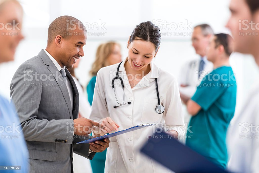 Doctor and African American businessman reading documents together. stock photo