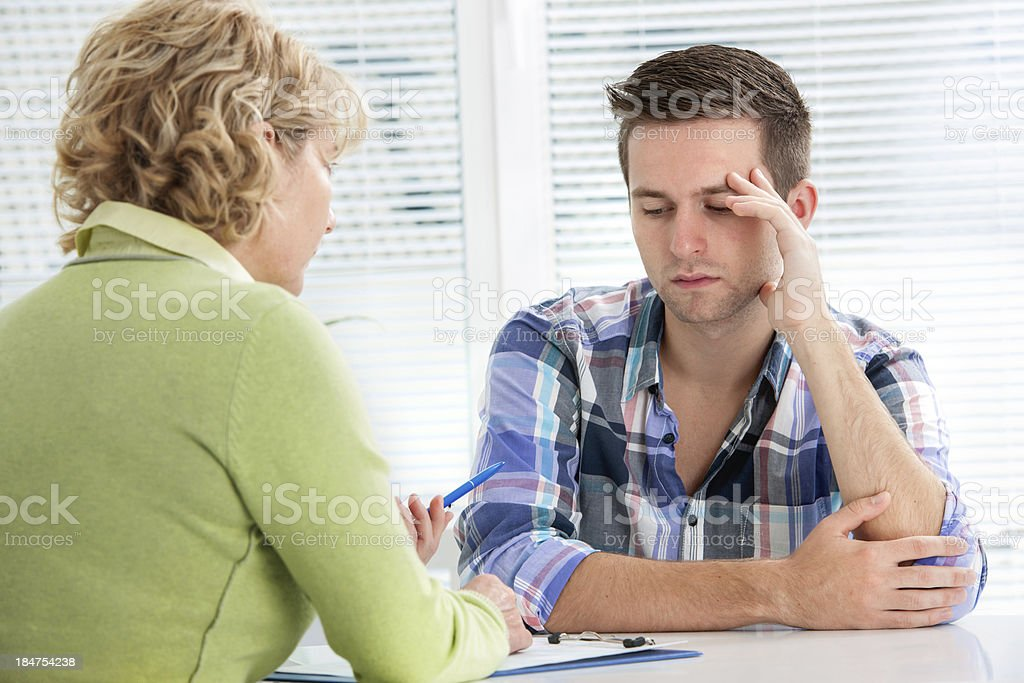 A doctor and an adult sitting at a table stock photo